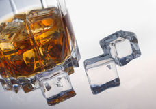 Glass of whiskey. Glass tumbler of whiskey with ice cubes Stock Image