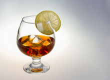 Glass of whiskey. Glass tumbler of whiskey with ice cubes and lemon Royalty Free Stock Photography