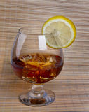 Glass of whiskey. Glass tumbler of whiskey with ice cubes and lemon Stock Images