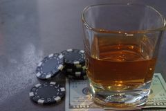 A glass of whiskey on a bank note, a poker game. royalty free stock photo