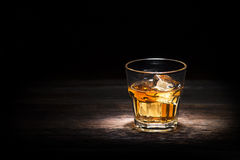 Whiskey. Glass of whiskey on wooden background close up Stock Image