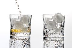 Glass of whisky. Glass with ice, one empty other filling with  whisky single malt, mmmm Stock Image