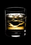 Glass of whisky on a black background. Glass of whisky with ice on a black background Stock Photography