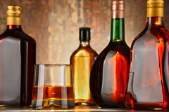 Glass of whisky and bottles of assorted alcoholic beverages Royalty Free Stock Photos