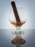 Glass whisky brandy cognac Cuban cigar background light gradient luster Royalty Free Stock Image