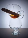 Glass whisky brandy cognac Cuban cigar background light gradient luster Royalty Free Stock Photo
