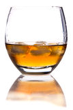 Glass of whisky with ice. Macro view of glass of whisky with ice cubes; reflected on white background Stock Image