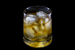 Glass of whisky with ice. On a black background Stock Photos