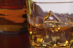 Glass of whisky with ice. Cubes and bottle, on the red wooden table Stock Photos