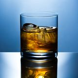 Glass of whisky with ice. Beautifully shined glass from whisky with ice is reflected in a glass table Stock Photos