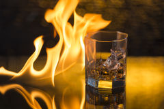 Glass of whisky with ice on a black background and fire flames Stock Image