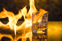 Glass of whisky with ice on a black background and fire flames Stock Photos