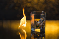 Glass of whisky with ice on a black background and fire flames Royalty Free Stock Photo