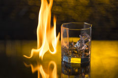 Glass of whisky with ice on a black background and fire flames Royalty Free Stock Image