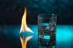 Glass of whisky with ice on a blue background and fire flames Royalty Free Stock Image