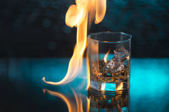 Glass of whisky with ice on a blue background and fire flames Royalty Free Stock Photos