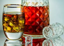 A glass of whisky with ice and bottle in a glass table. Reflecting the glass Royalty Free Stock Photography