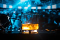 Glass with whisky with ice cube inside on dj controller at nightclub. Dj Console with club drink at music party in nightclub with. Disco lights. Selective focus stock photos