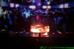 Glass with whisky with ice cube inside on dj controller at nightclub. Dj Console with club drink at music party in nightclub with. Disco lights. Selective focus stock photo