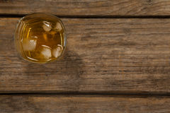Glass of whisky with ice cube on wooden table Royalty Free Stock Photo
