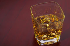 Glass of whisky with ice cubes. On the red table Stock Photos