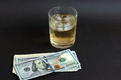 A glass of whisky with ice cubes on black color table background. royalty free stock photo