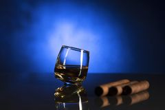 Glass with whisky isolated over blue background royalty free stock photo