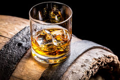 Glass of whisky and old wooden barrel. Isolated on a black background Royalty Free Stock Image