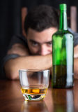 Glass of whisky with an out of focus drunk and depressed man Stock Photo