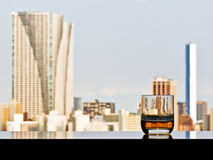 A glass of whisky with panoramic city view Stock Photography