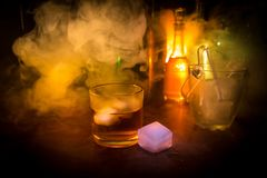 Glass of whisky on wooden bar closeup with bottles blurred view on dark background with light and smoke. Single glass of whisky on. Ice with a reflective wooden royalty free stock photos