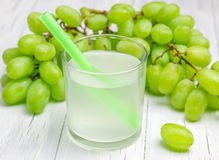 Glass of white grapes juice and grapes. On background Royalty Free Stock Photography