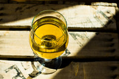 Glass of white Muscat wine with rich yellow ochre copper glow on a wood box in sunrays Stock Images