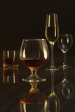 Glass with white, red wine and cognac or whisky on mirror table. Celebrities composition. selective focus Royalty Free Stock Photography