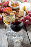 Glass of white and red wines, appetizers on a wooden background Stock Photo
