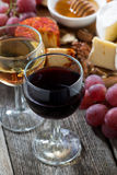 glass of white and red wines, appetizers on a wooden table Royalty Free Stock Images
