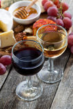 Glass of white and red wines, appetizers on a wooden table Royalty Free Stock Photos