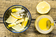 Glass of white sangria with lemon and honey jar Stock Image