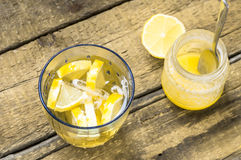 Glass of white sangria with lemon and honey jar Stock Images