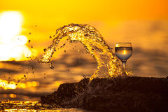 Glass of white vine with reflections of sun and sea on the backg Royalty Free Stock Photos