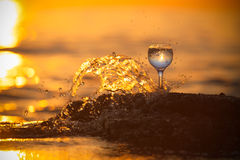 Glass of white vine with reflections of sun and sea on the backg Royalty Free Stock Photo