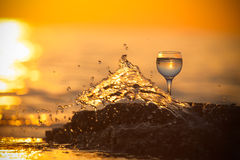 Glass of white vine with reflections of sun and sea on the backg Royalty Free Stock Images