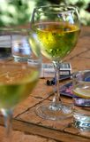 Glass with white wine. A little table with the glasses filled by white wine, cigarettes and a glass of cold, pure water Royalty Free Stock Photography