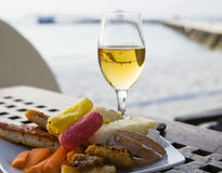 A glass of white wine. And a plate with snack royalty free stock photography