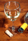 Glass of White Wine. This is an image of a glass of white wine with the top of a wine bottle and a cork royalty free stock photos