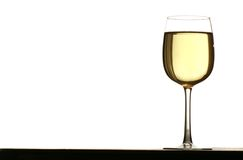 Glass of white wine. Backlit against white background Stock Photos