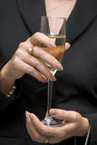 Glass with white wine. A glass the filled wine in hands of the business woman Stock Photography