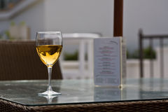 Glass of white wine. And restaurant menu Stock Images