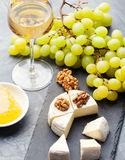 Glass of white wine and assorted cheese with grape on a slate background Copy space Royalty Free Stock Photos