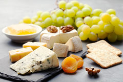 Glass of white wine and assorted cheese with grape on a slate background Copy space Royalty Free Stock Images